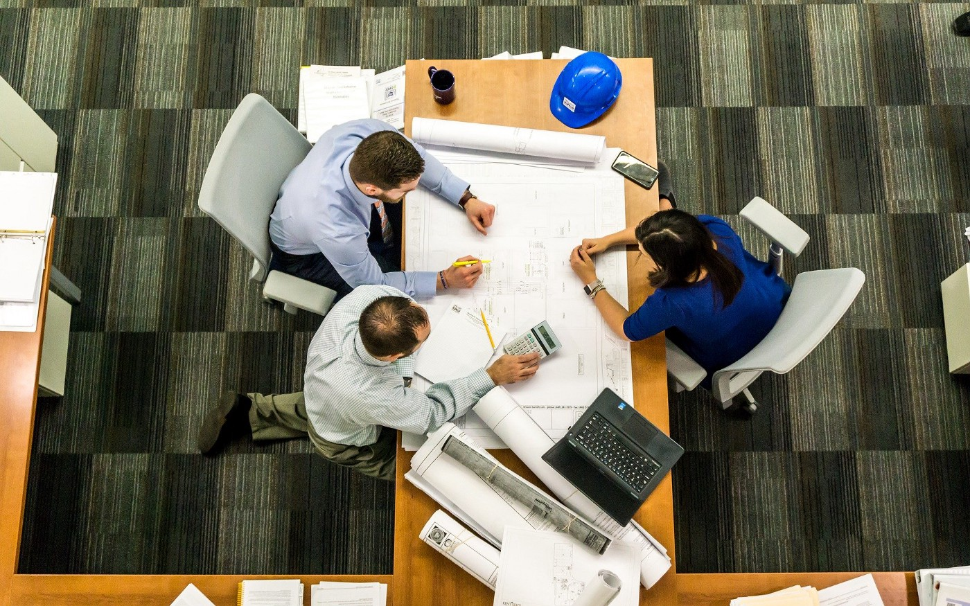 Picture looking down at a table with three people looking over a drafting plan.