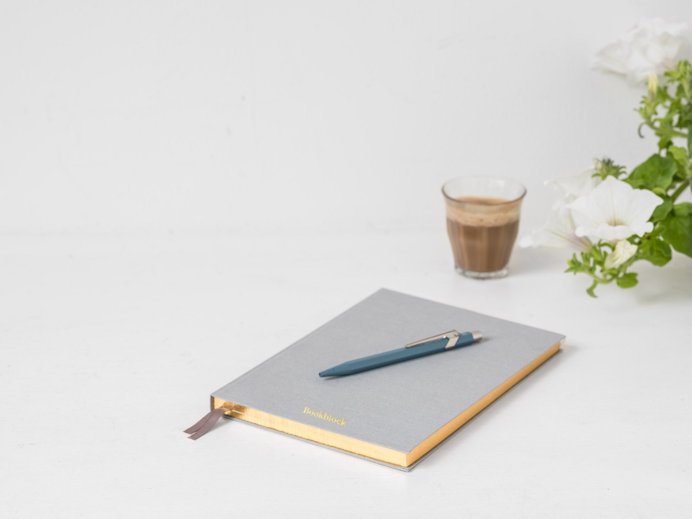 An image of a notebook with a pen on top of it and a glass of coffee next to it.