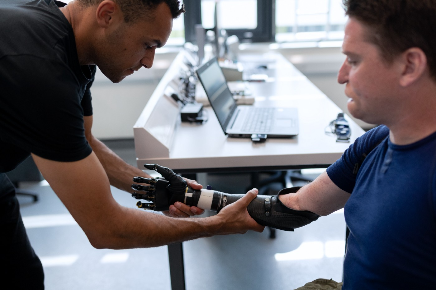A man in a wheelchair having a prosthetic lower arm fitted by a prosthetist