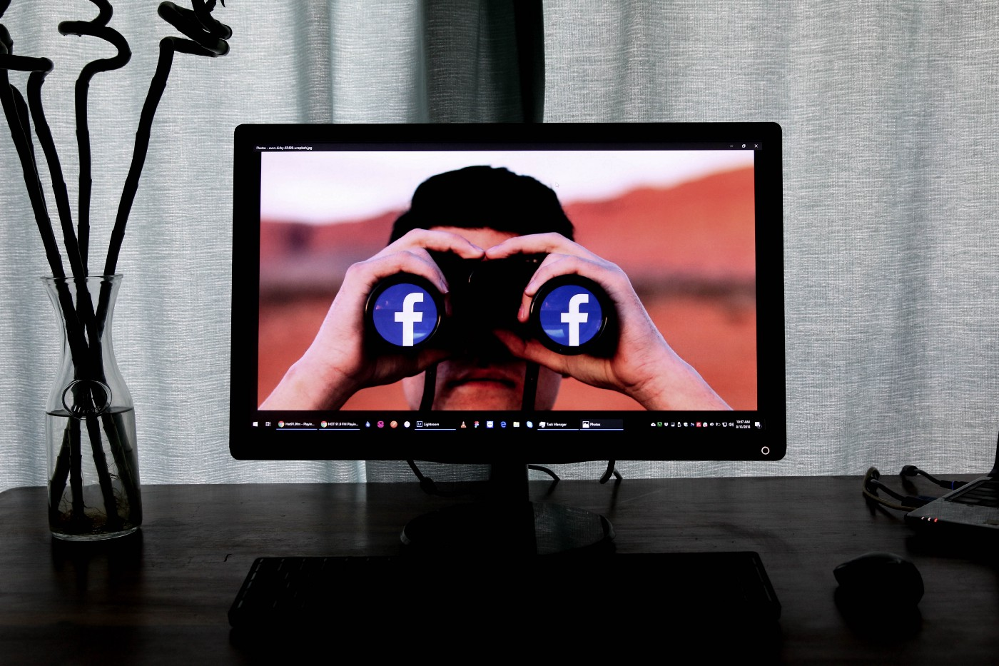 A computer monitor with the image of a person looking through binoculars with the Facebook logo in the lenses