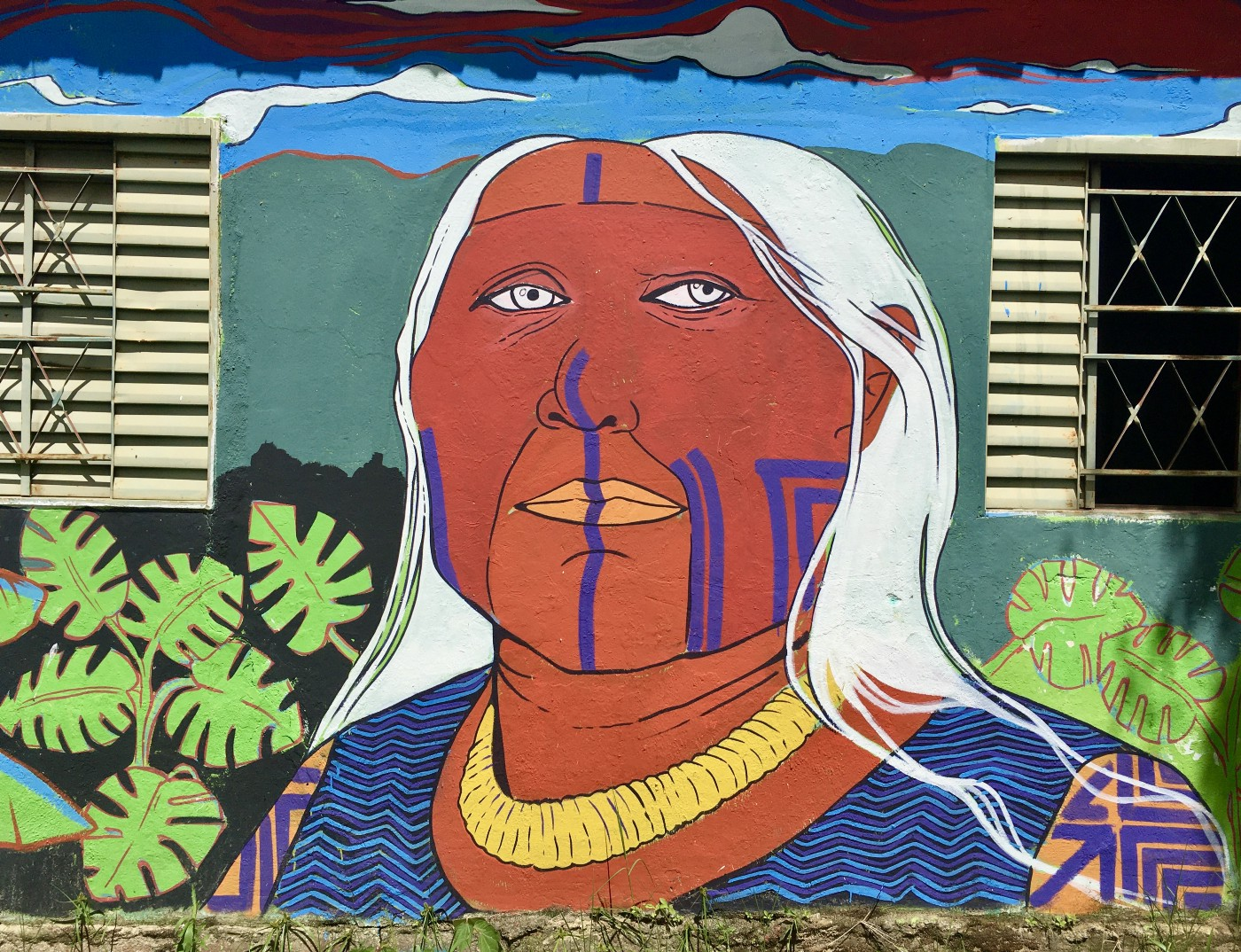 A colourful wall mural of an elder's face. They have long white hair and markings on their left cheek and from nose to chin in purple.
