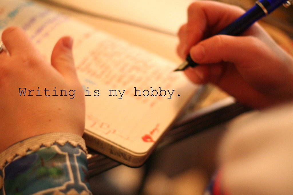 """notebook with a person writing using a fountain pen; text over says """"Writing is my hobby."""""""