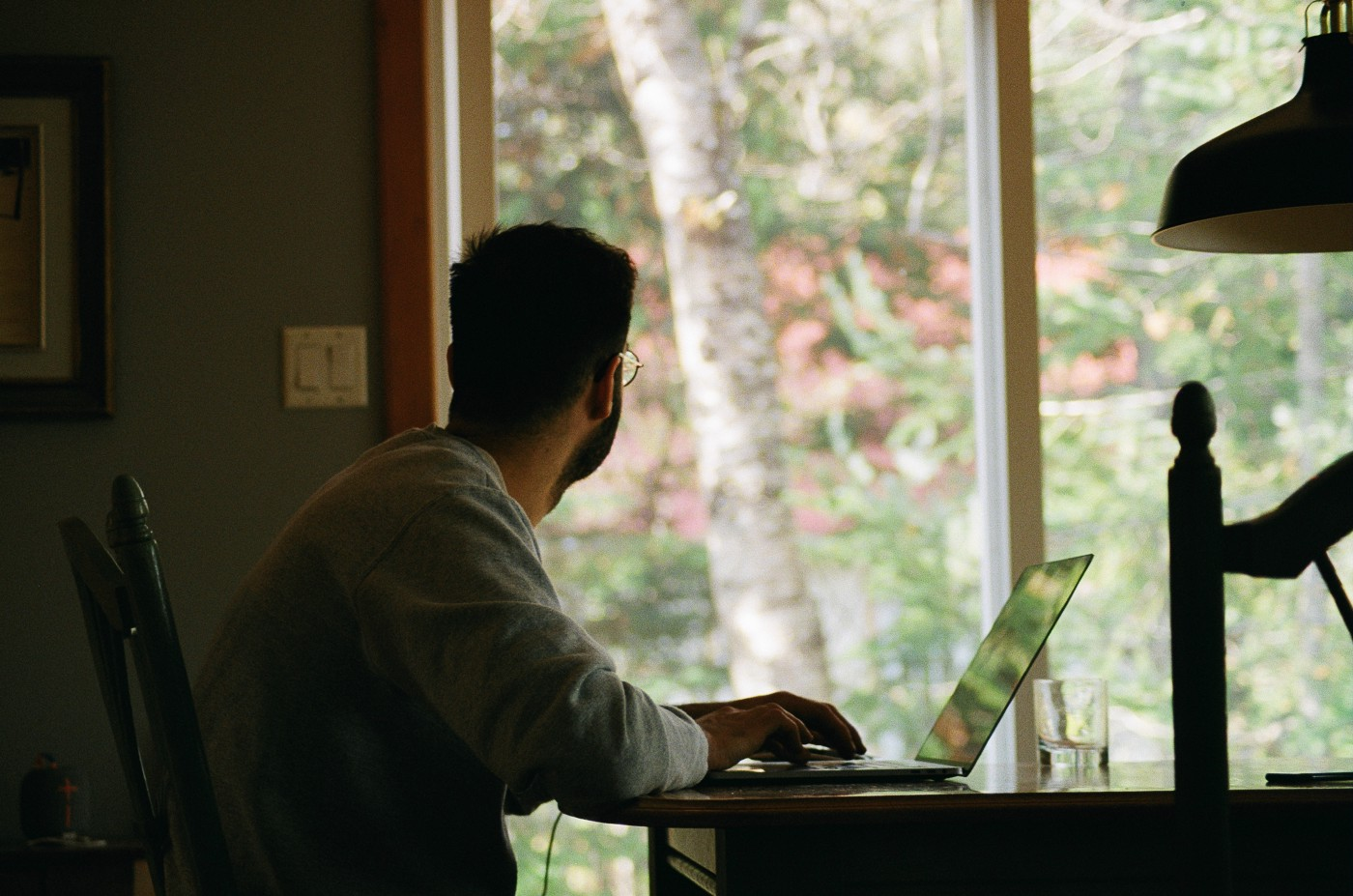 A guy working from home. Looking out of the window, involved in deep thought.