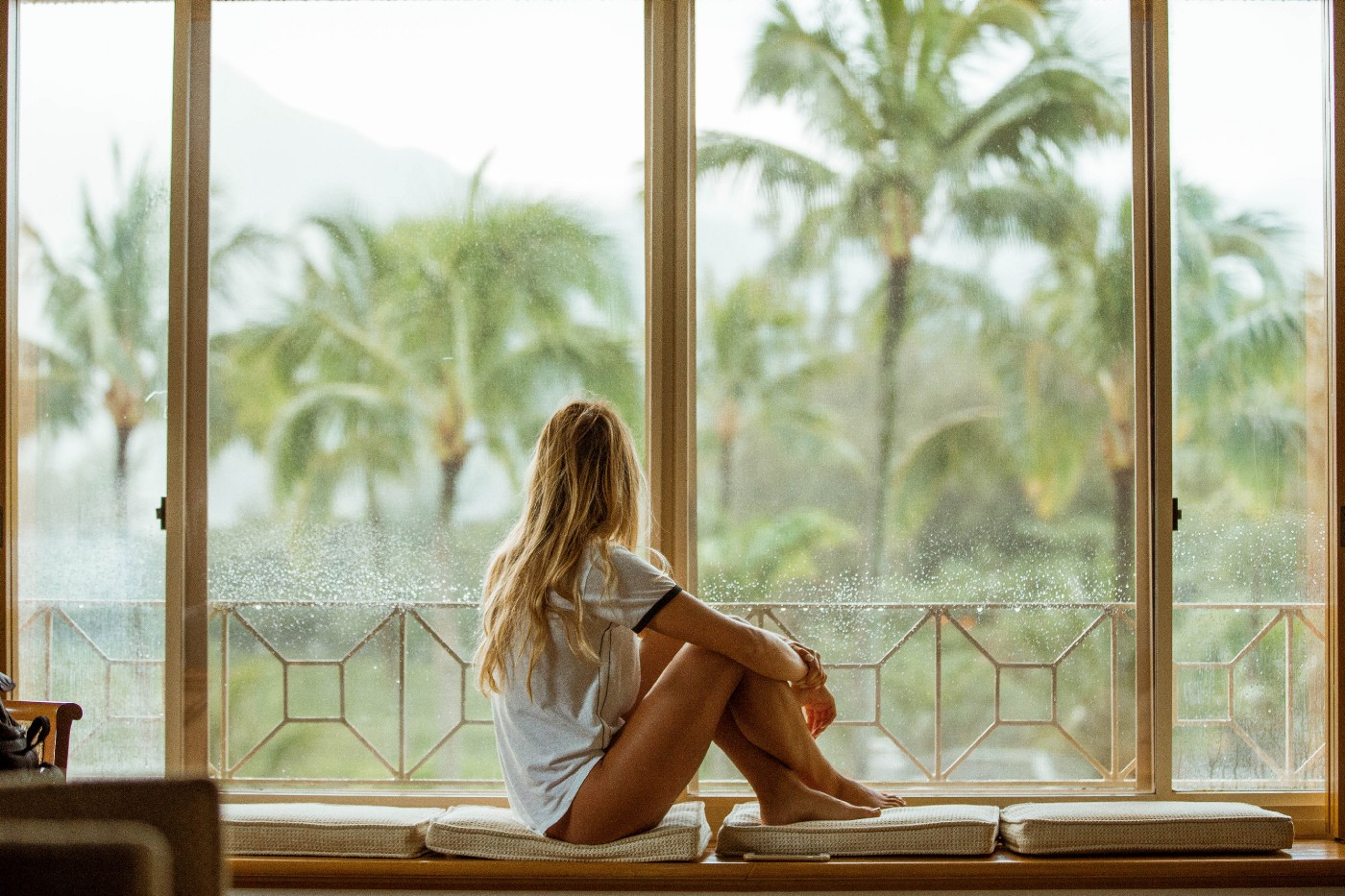 Girl sits by a window looking at a hot, tropical view.