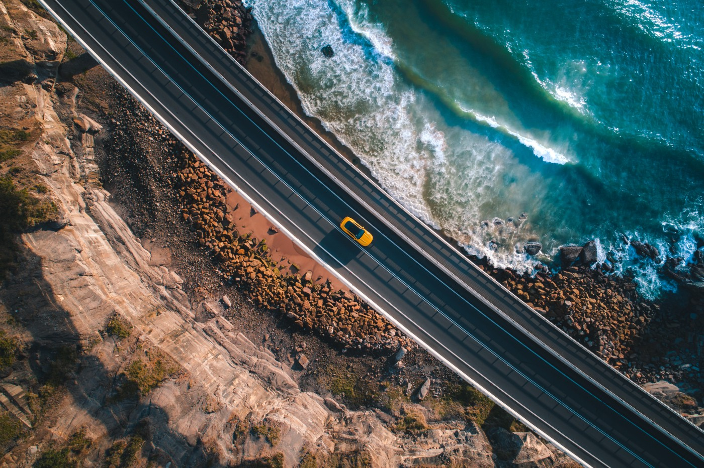 aerial photo of car driving on a highway next to the ocean