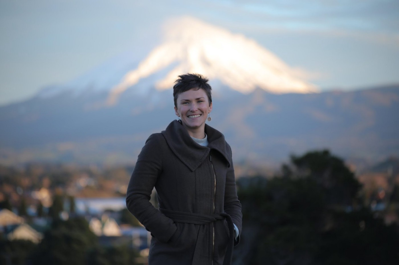 Amanda standing outside with the maunga (mountain) behind her at sunset