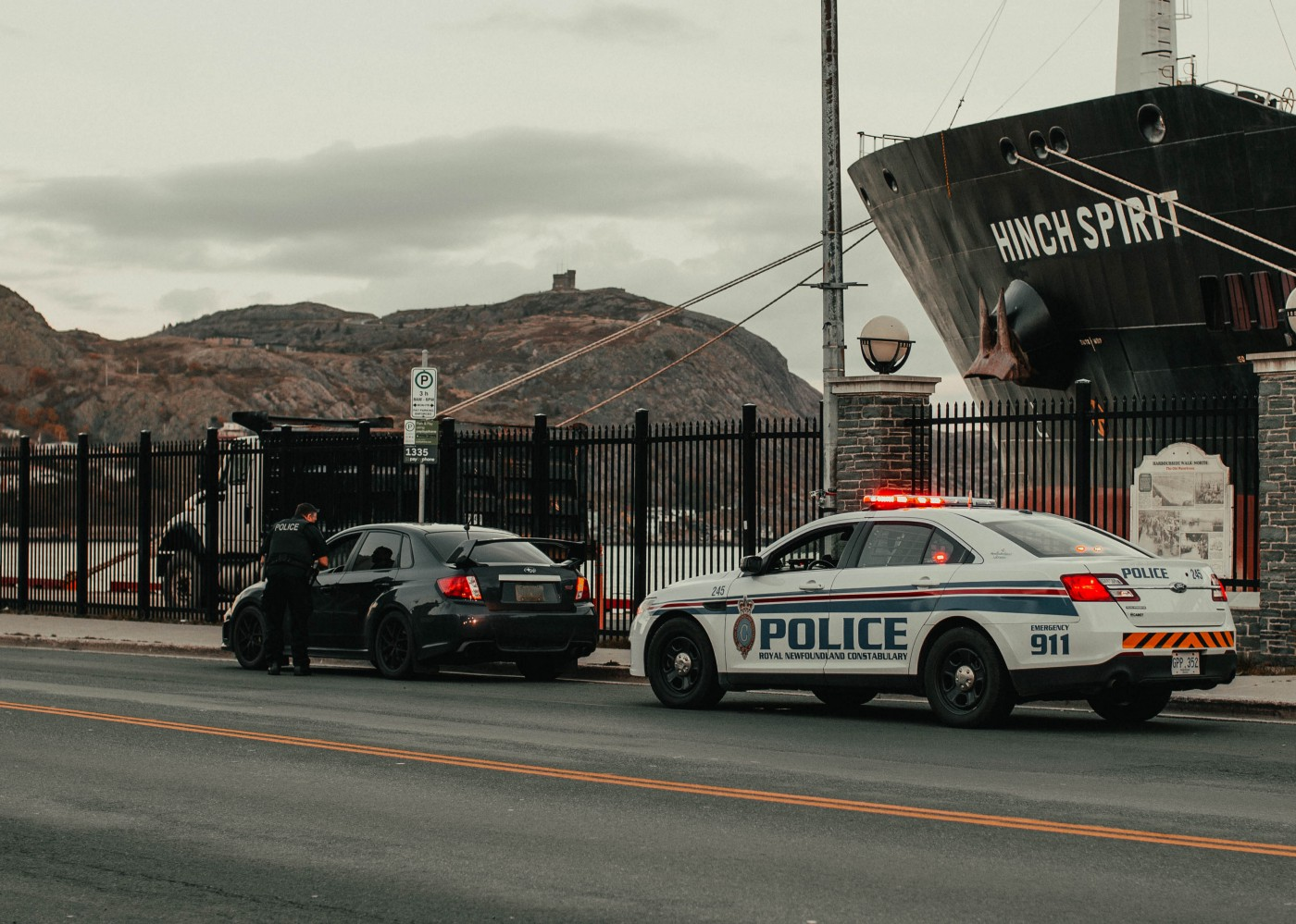 """Police officer questioning a stopped motorist, incidentally with his car pulled over in front of a large ship """"Hinch Spirit"""" and lovely cliffs in the background"""