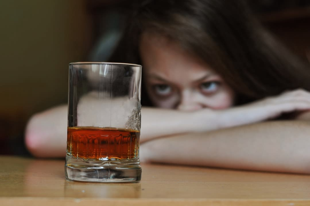 Woman looking at an alcoholic drink.