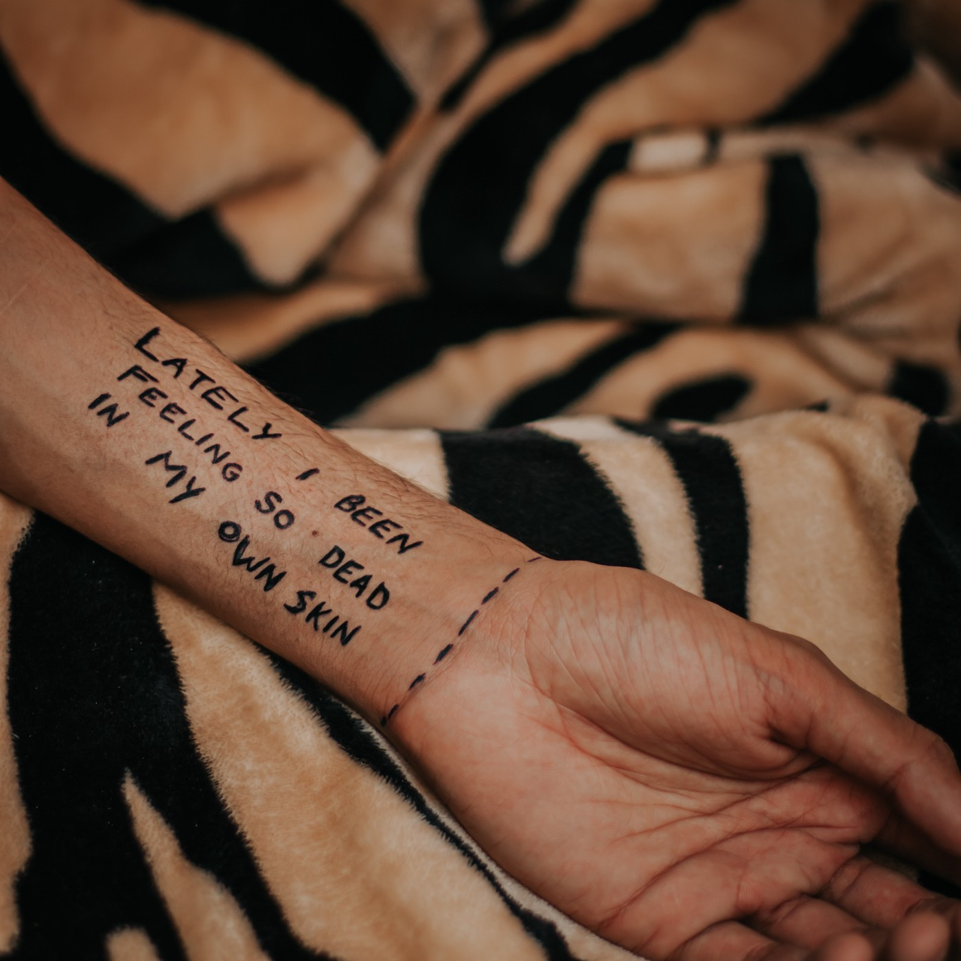 A hand with text written as: LATELY I BEEN FEELING SO DEAD IN MY OWN SKIN