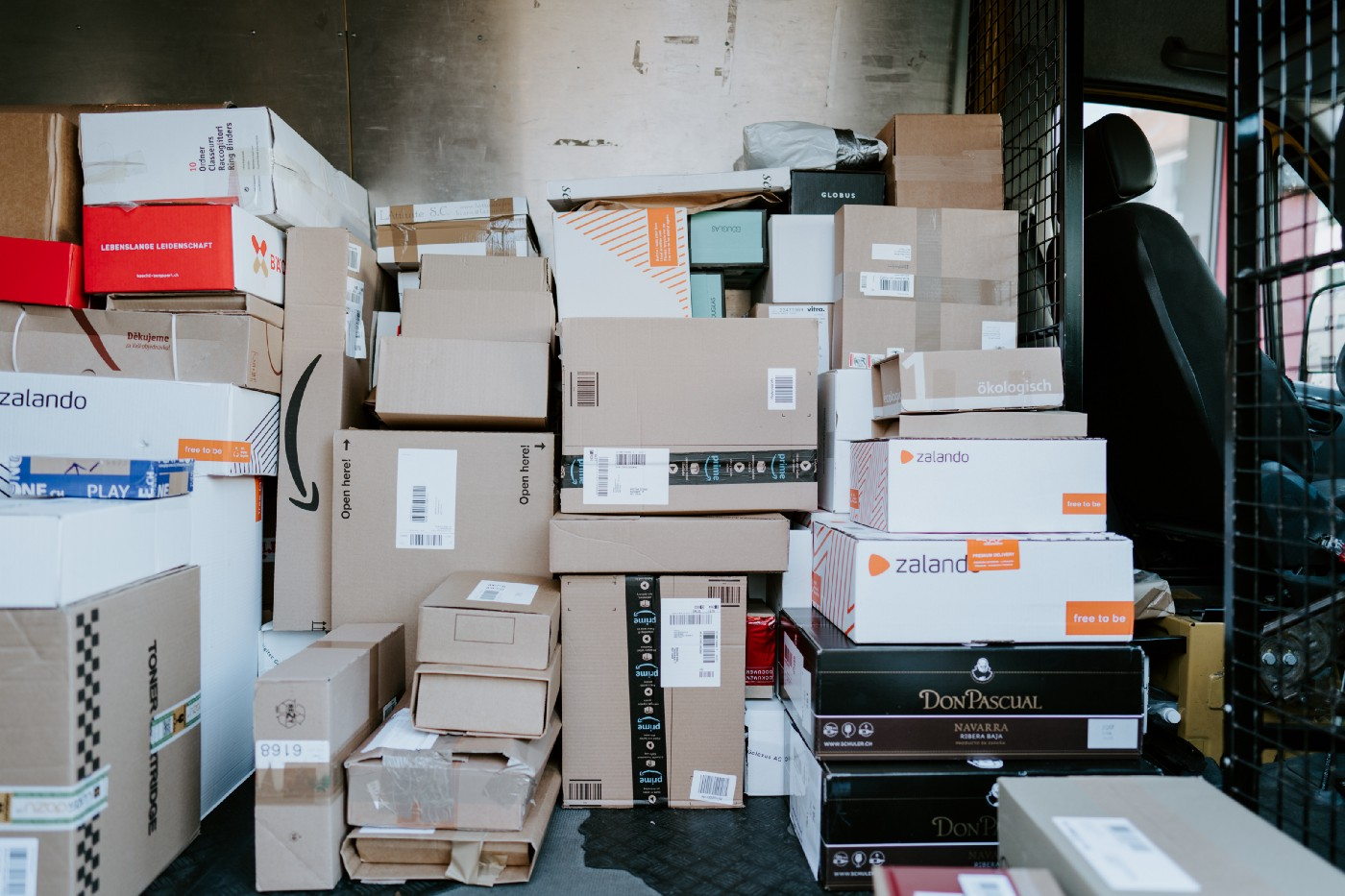 Dozens of packages piled up in a delivery truck.