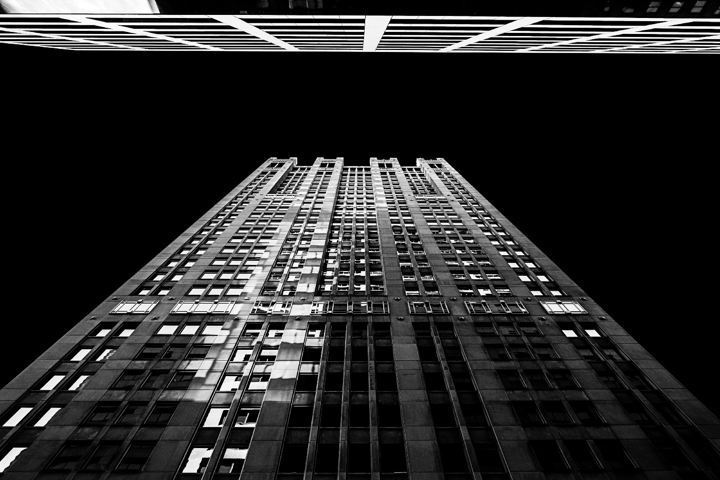 Black and white picture of a skyscraper, photographed from the bottom looking up at the building reaching to the sky.