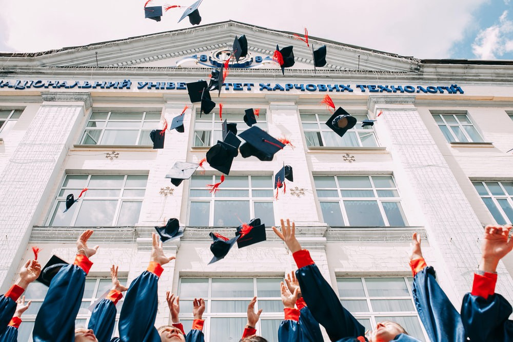 students throwing graduation caps into the air in front of a college building