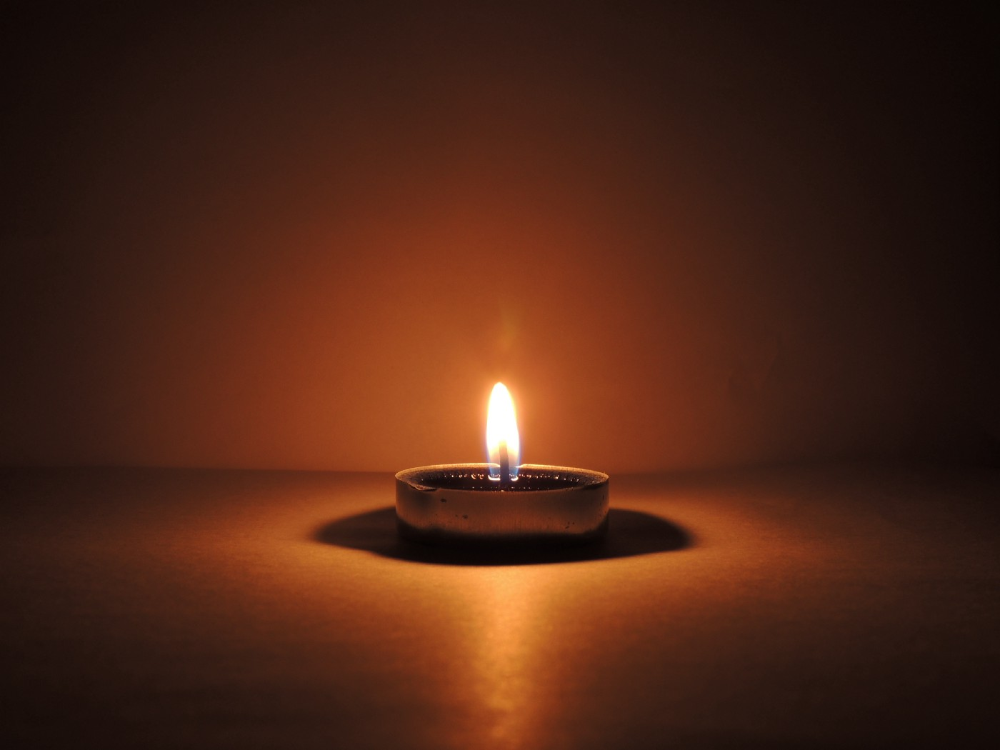 A single lighted candle glowing in a dark room.