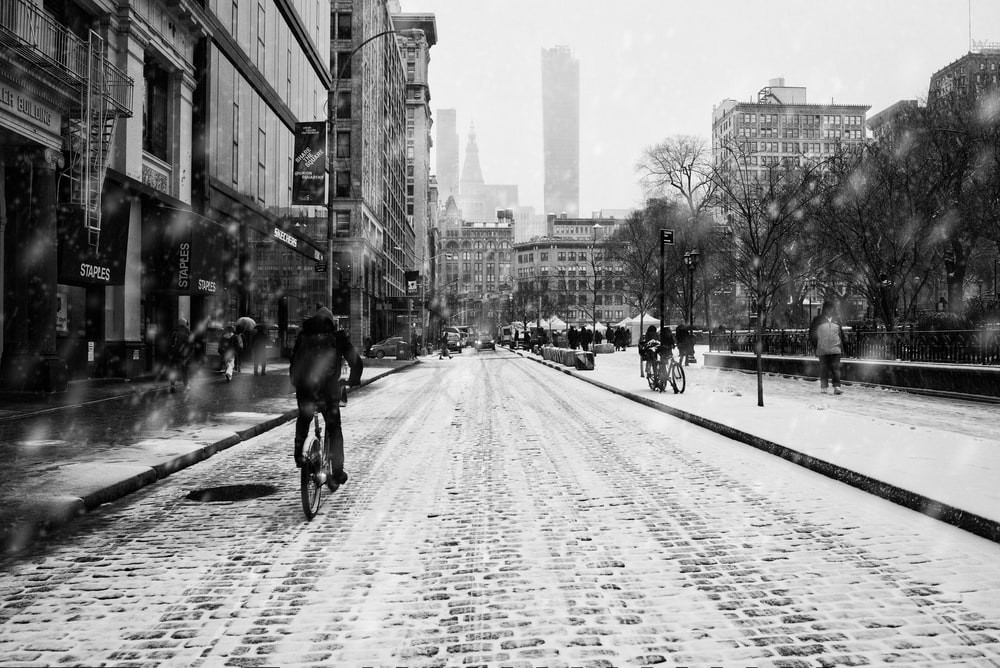 A cyclist bikes down a snow-blanketed union square as buildings loom in grey silhouette.