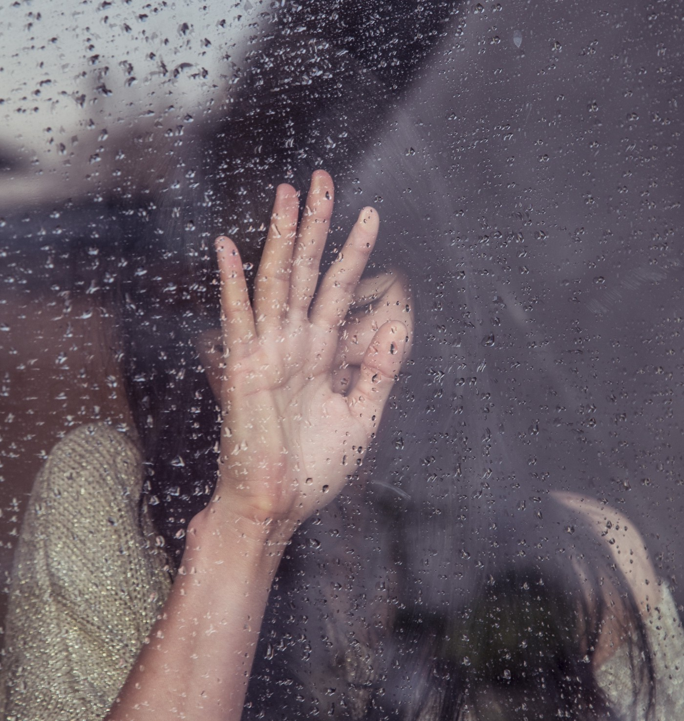 Distraught woman with hand covering part of her face pressed to a rainy window.
