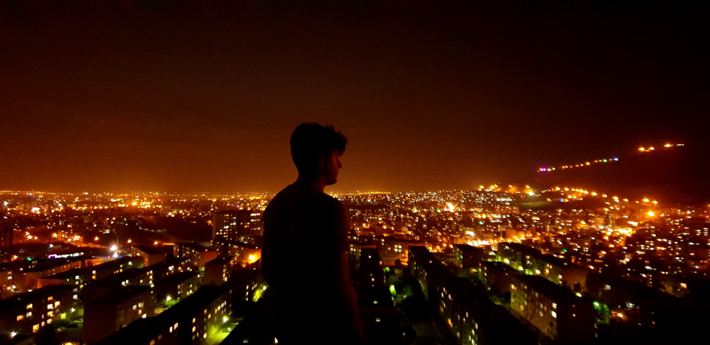 A man standing alone with the city in the background.