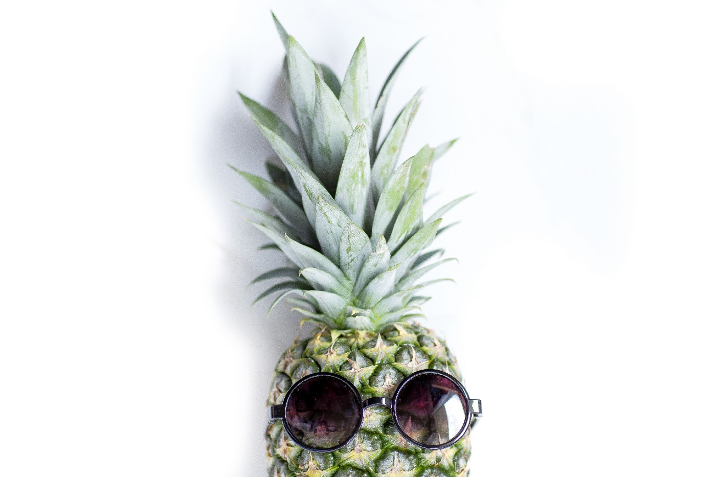A pineapple with round sunglasses on it, on a white background.
