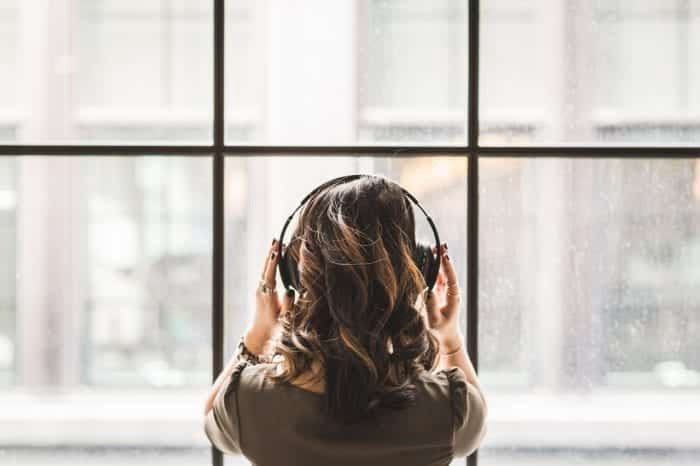 Back of woman's head wearing headphones looking out a window