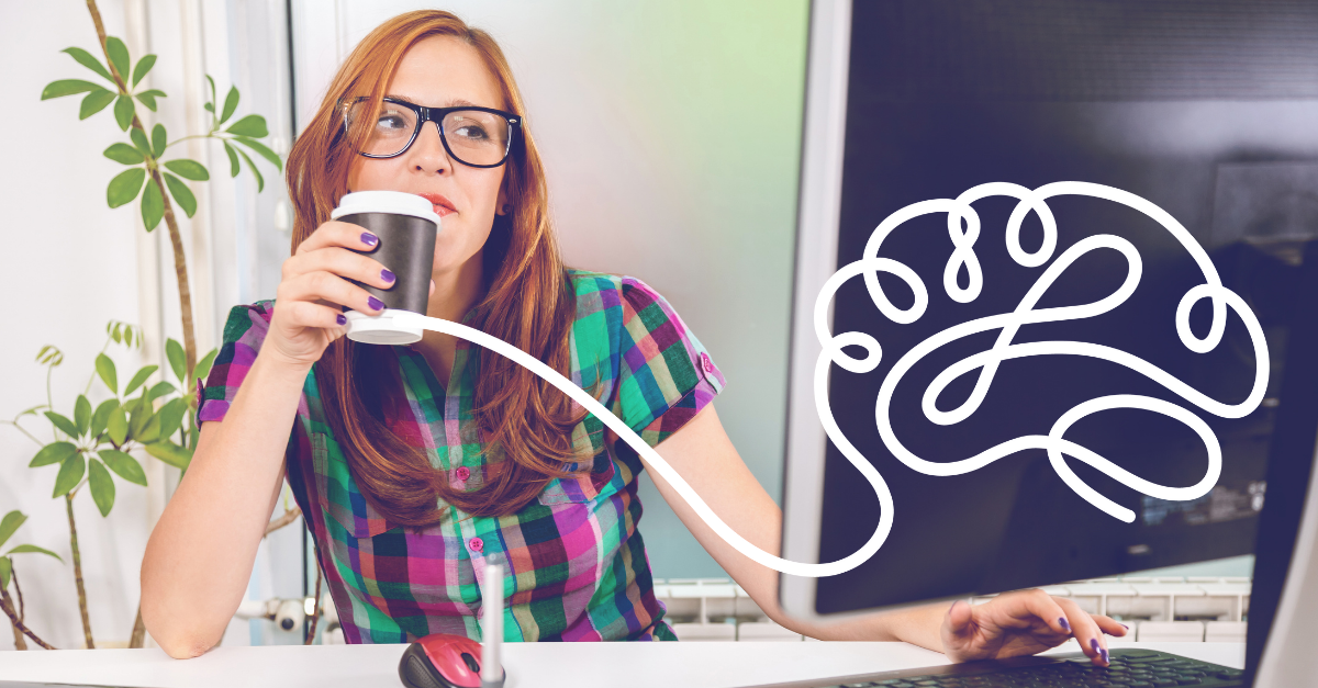 Woman with glasses enjoying a coffee while typing