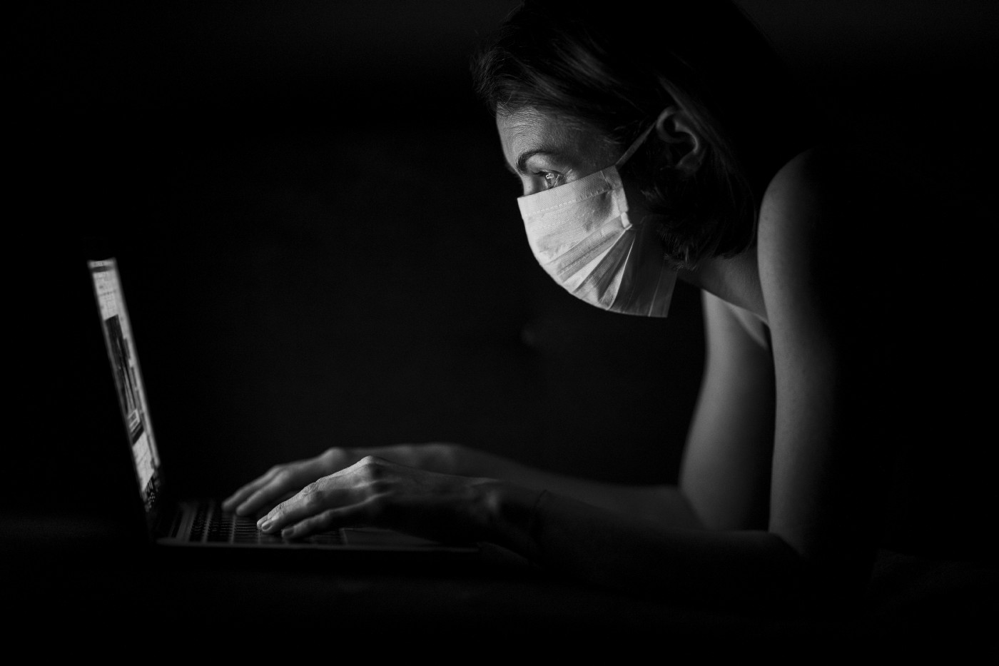 Masked girl working on her laptop
