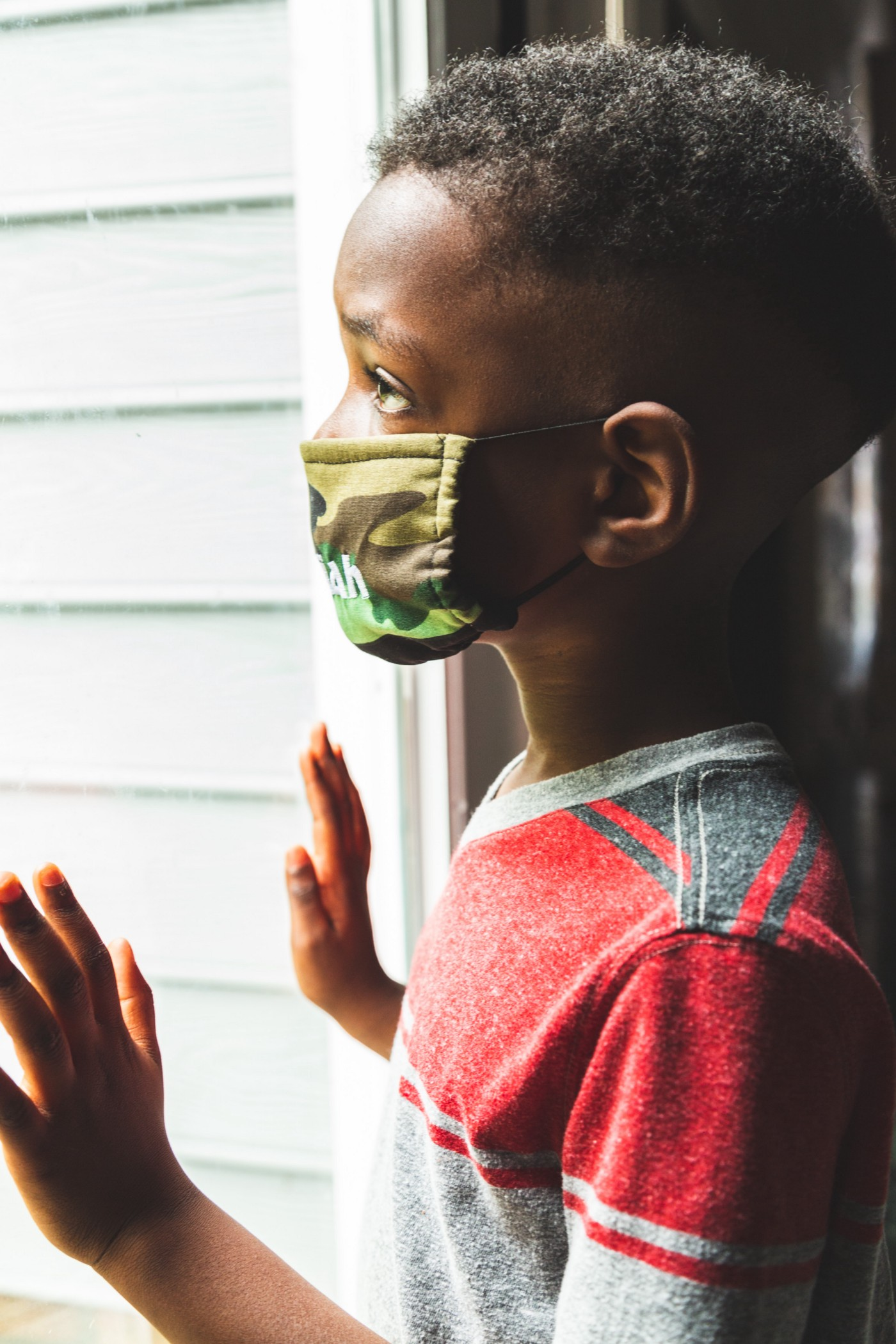 Boy wearing a face mask and looking out a glass door.