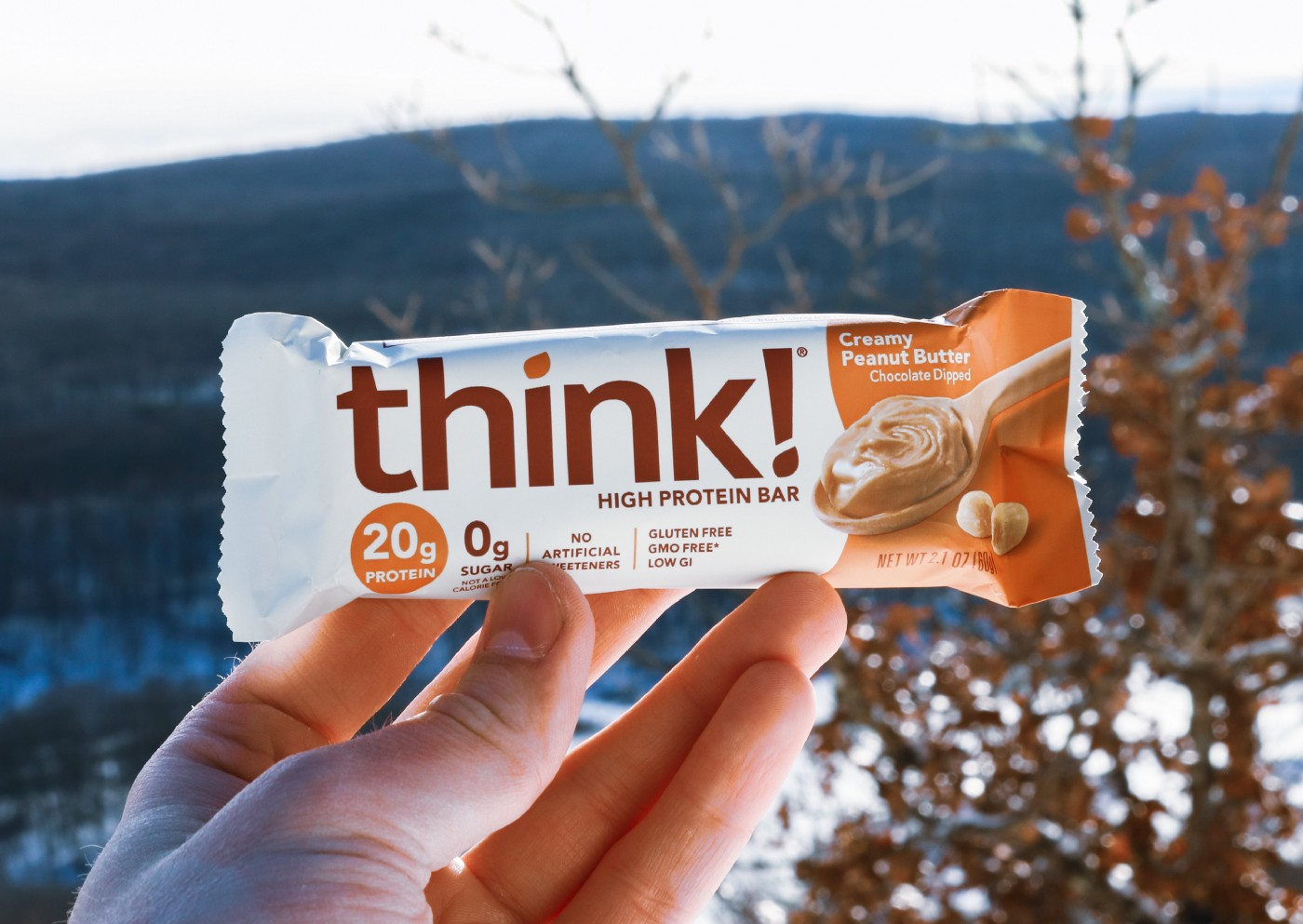 a person holding a Think Creamy Peanut Butter Bar. in the background you see a mountain and trees