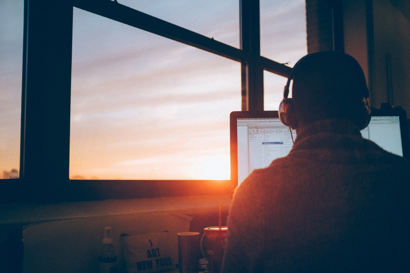 Man working on laptop at sunset in front of a large window