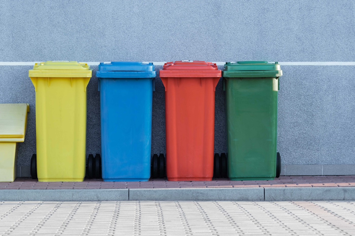 four coloured waste bins in a row