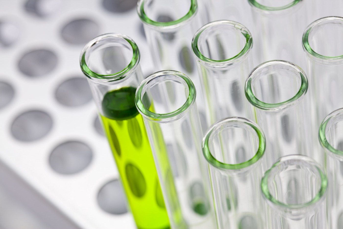 a rack of test tubes, one of which is filled with a green liquid