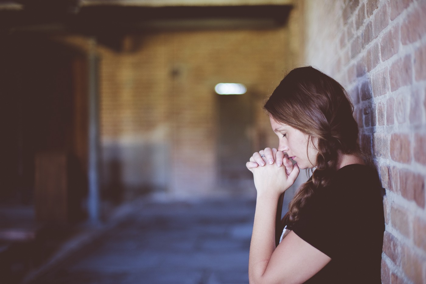 Woman with plaited braid praying with back to a brick wall.