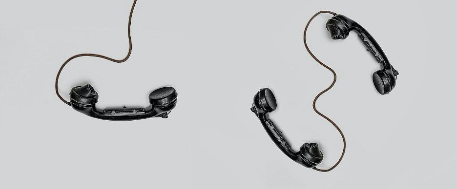 black telephones with swirled wires on a grey background