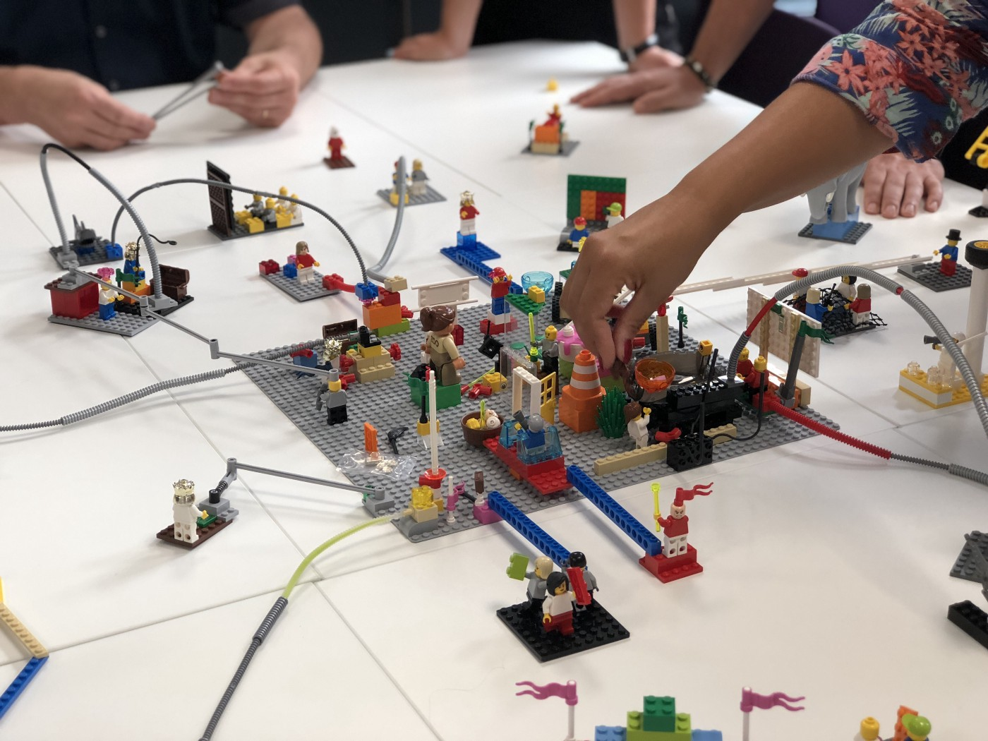 Multiple people with multiple Lego sets in various stages of build