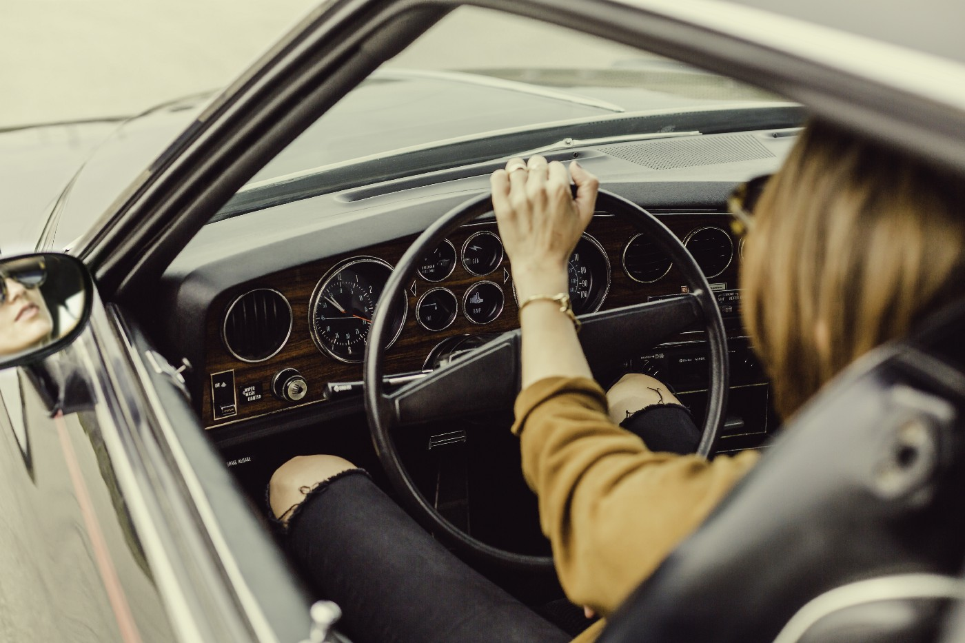 Woman holding steering wheel and driving a car.