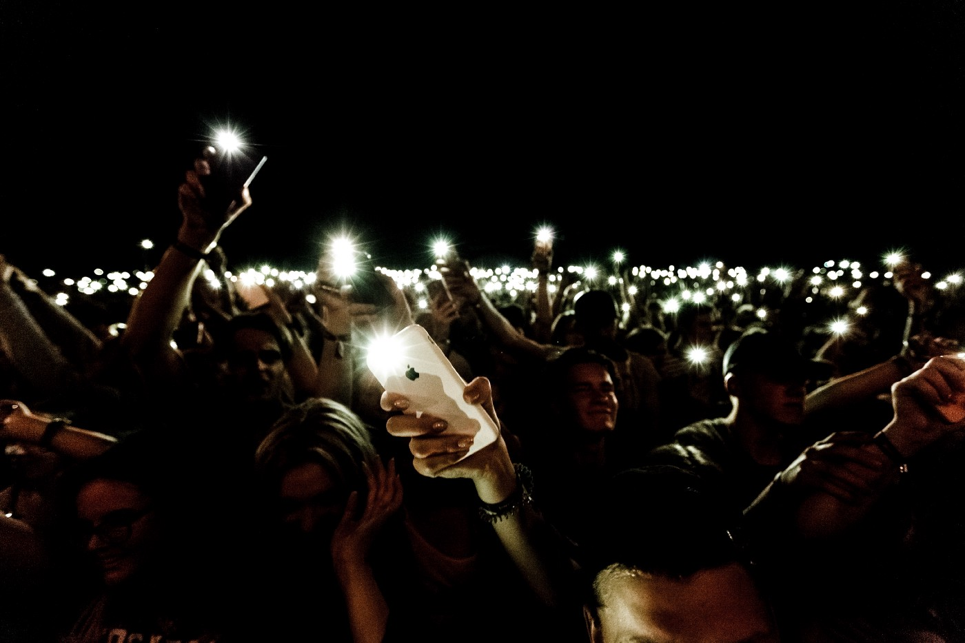 People hold up their phones with their flashlights on at a concert.