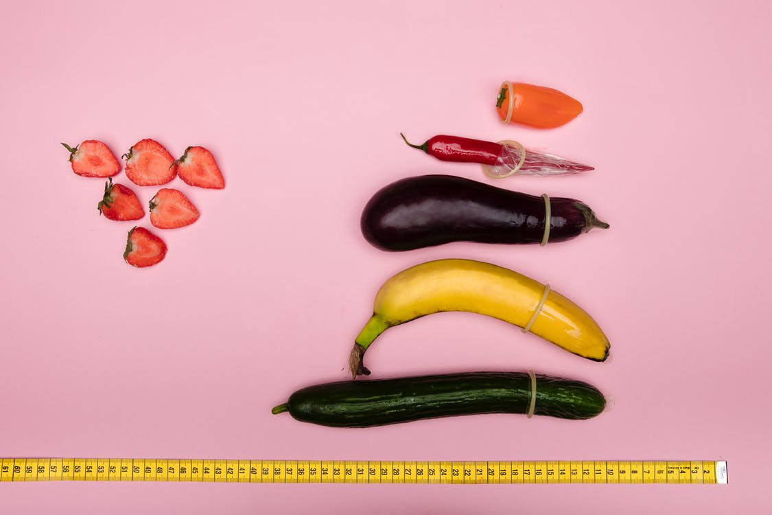 Different phallic vegetables lined up with condoms and a ruler, next to strawberry slices. #sex #penissize #sizedoesntmatter