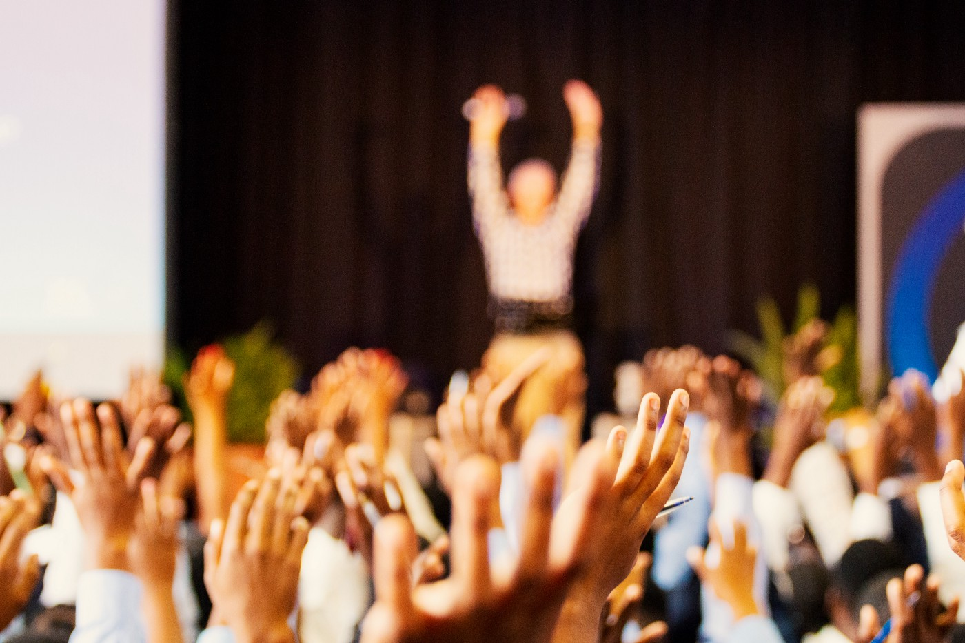 Scores hands raised in the air and a speaker with a microphone in the distance, on stage, hands raised and addressing the room