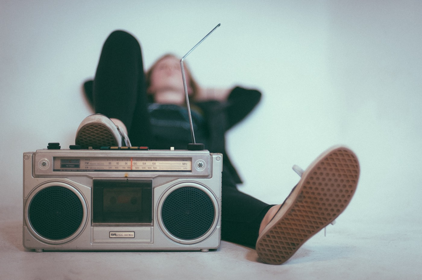 Man laying down with his sneaker up on a boom box. Background is plain white.