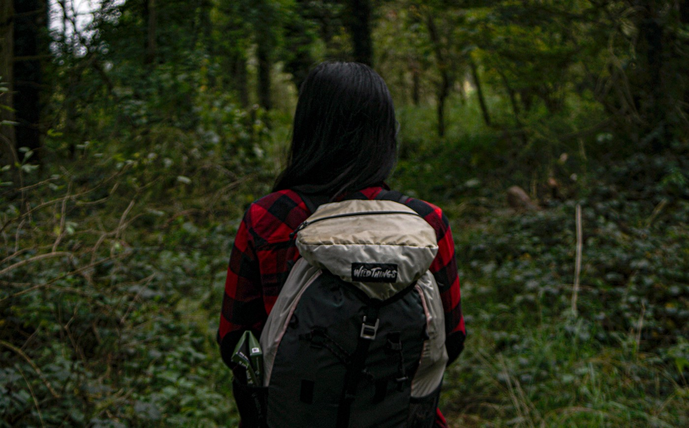 Person with long black hair standing in a forest. Wearing a hiking backpack, and red flannel shirt.