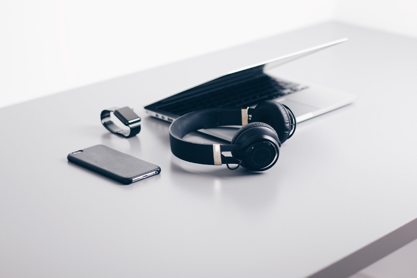 A laptop, a mobile phone, a smartwatch and a pair of headphones