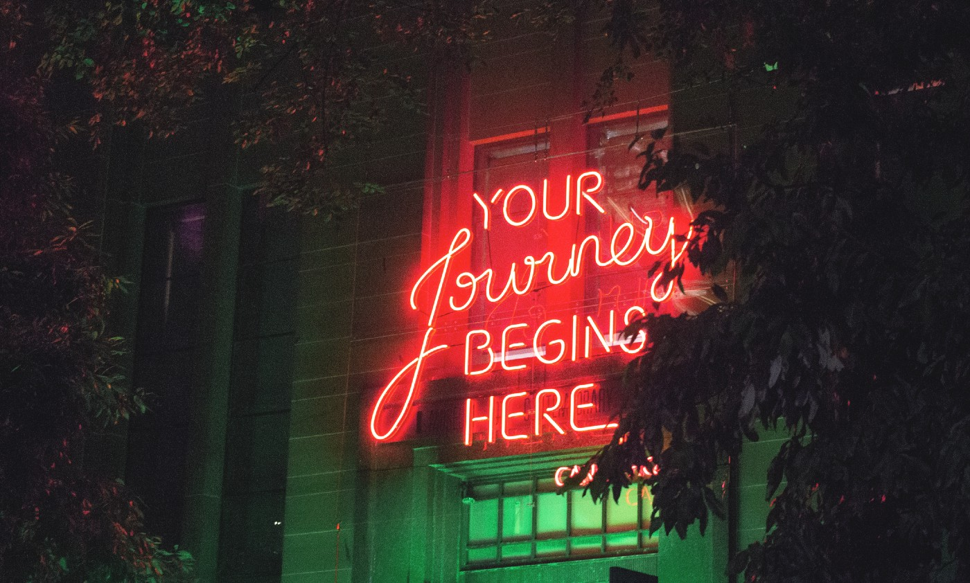 """A red neon sign over a neon green entry that reads, """"Your Journey BEGINS HERE""""."""