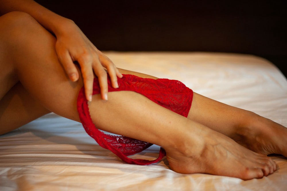Dainty underwear around the ankle of naked woman's legs