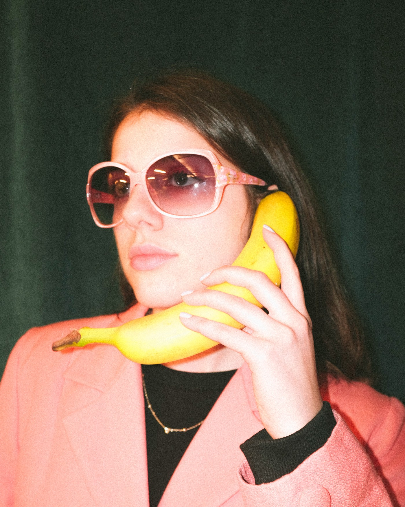 Person holding banana as a telephone.