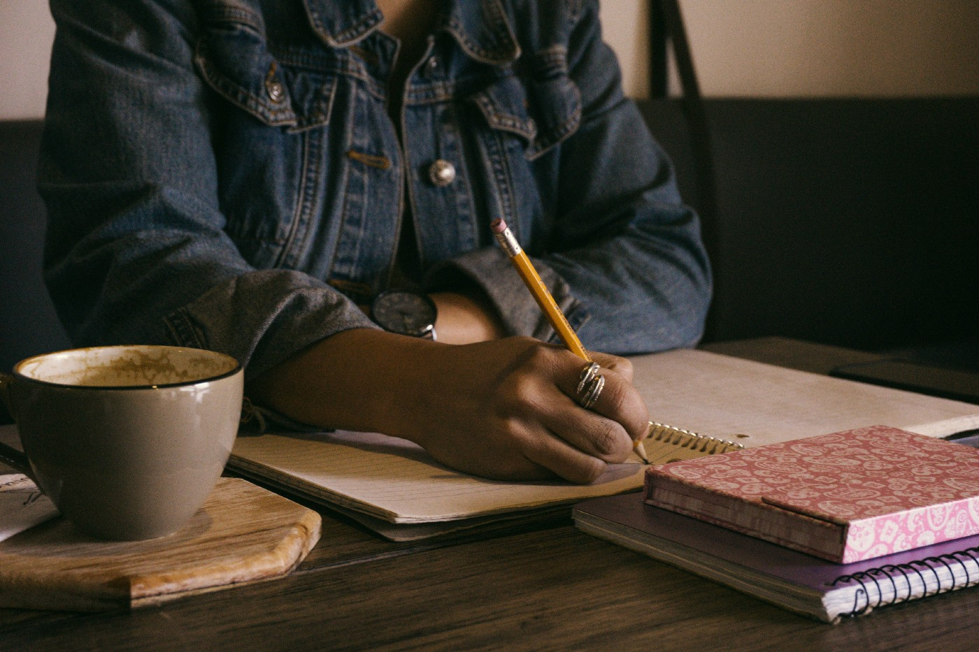 Person writing in journal at a table with an empty cup of coffee