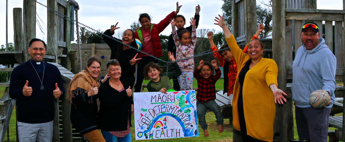 """A group of seven kids standing and sitting on a playground, flanked on either side by two adults. Everyone is smiling and enthusiastic, holding out their arms and showing peace signs and thumbs up. One man is holding a rugby ball. A child in the centre of the frame holds a home made poster that says """"Māori self-determination for health"""" that has been decorated in bright colours, including a rainbow."""