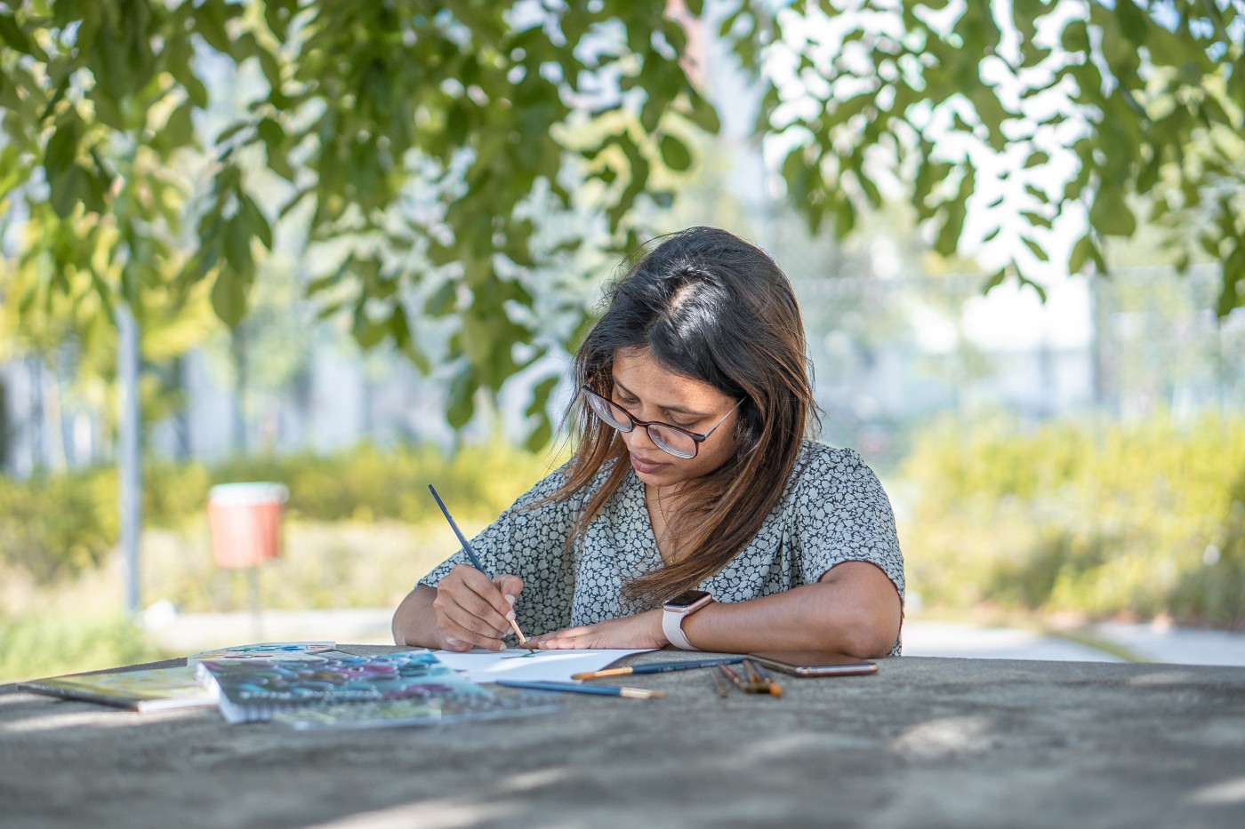 A girl with spectacles, sitting and writing on a table under the shade of a tree.