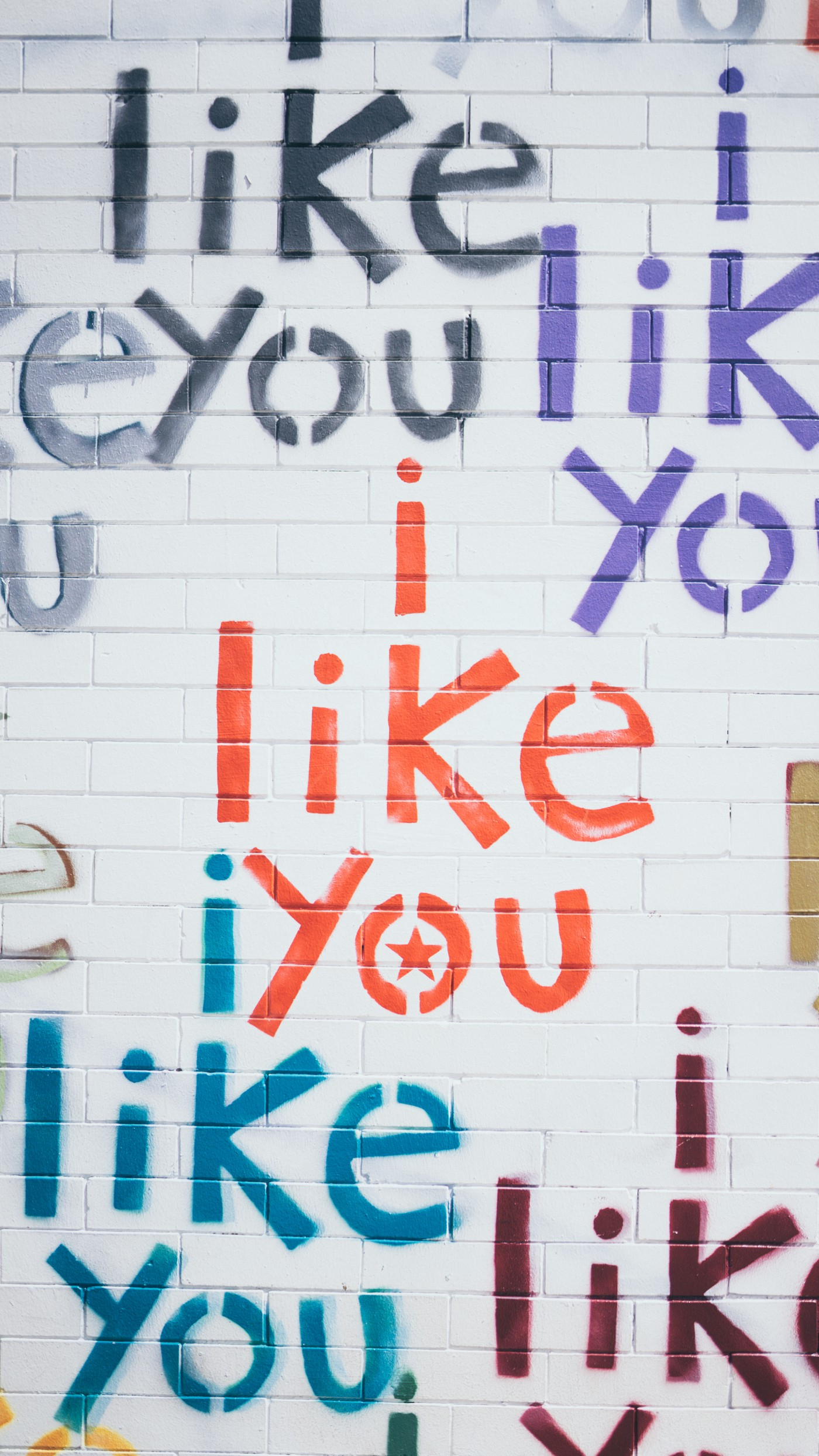 words i like you on white brick wall in different colours