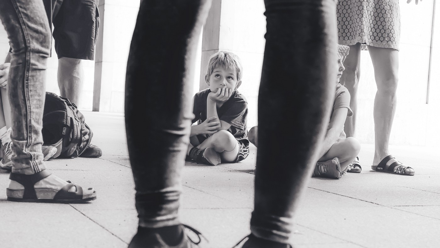 Black and white image of child sitting on floor looking at adults