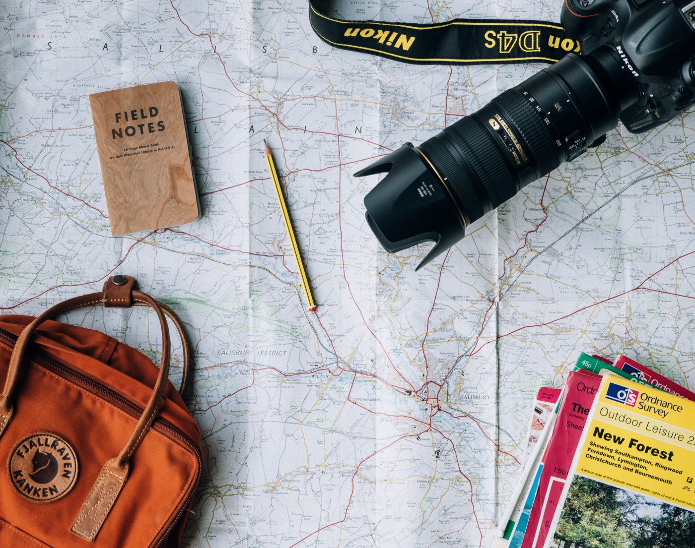 photo of map, backpack, camera, pamphlet posted on Dr. James Goydos 2021 article about vacation.