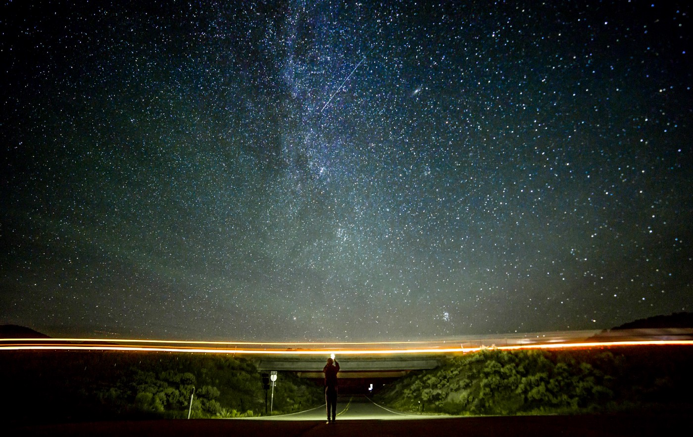 A wide shot of a person standing in the middle of an empty highway road at night. They are holding up a light in their hands as they are being shrouded by darkness. The majority of the scene is taken up by a deep night sky, coloured blue by a blanket of dazzling stars and an orange stripe of sunset above the shrubs that line the road. A shooting star is visible directly above them. Our writing can be more interesting than our boring lives. Rambling Rose. Tim Denning.