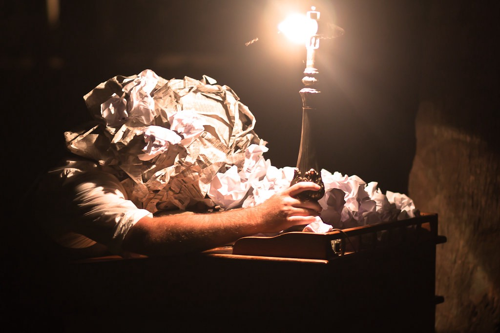 A man with a ball of crumbled papers for a head has defeated body language over a desk while grasping a lamp with no shade, the bare bulb appearing to be crooked in the socket.